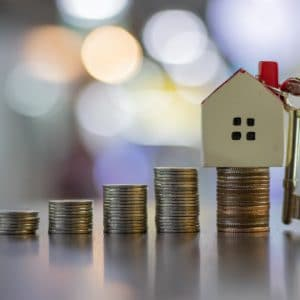 House and coins stack for saving to buy a house. Property investment and house mortgage financial concept. Hand putting money coin stack with house. Investment and retirement concept.