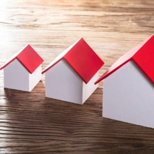 Increasing House Models With Red Roof In A Row On Wooden TableIncreasing House Models With Red Roof In A Row On Wooden Table