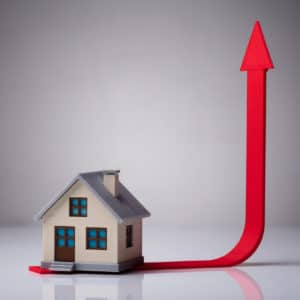 Close-up Of House Model On Red Arrow Showing Upward Direction