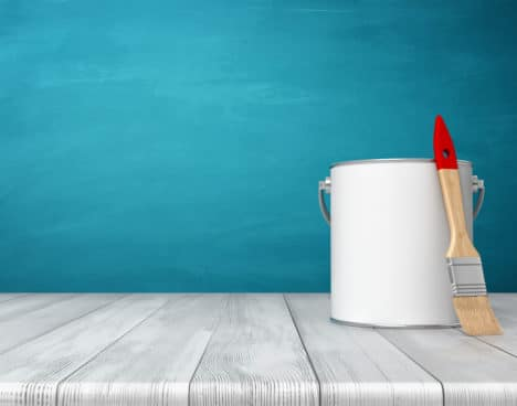 3d rendering of a metal paint can on a wooden desk with a new clean brush leaning on its side. Art supplies. DIY and renovation. Building and decorating.